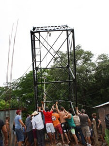 Volunteers pushing up the water tower for the Gigante Community Health Center. Photo: Angela R. Kirwin