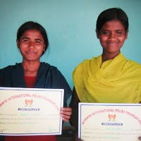 Two women who graduated from the Sewing Center's vocational training program holding up certificates.