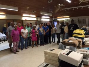 Father Clark and his congregation delivering supplies to 30 elderly couples whose homes and contents were badly damaged by the flood waters.