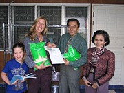 Angela Kirwin giving aid relief to orphanage with money raised from Ventura College. These KIRF funds were used to purchase food like rice and cooking oil. This photo shows Angela holding rice with orphanage women, man and child