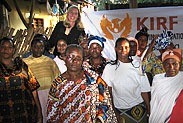 "KIRF assisted two women's cooperatives (called ""mamas groups"" in Tanzania) by supporting their entrepreneurial projects with in-kind donations and funding. Here is an image of Angela with one of these groups holding up the KIRF sign behind them."